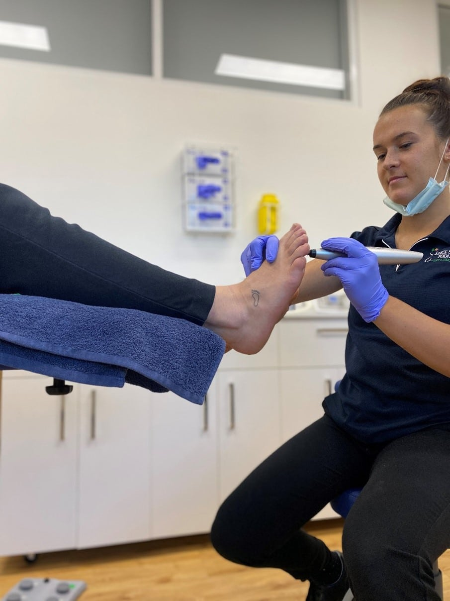 Lady Cleaning The Foot — Podiatrists in Alice Springs, NT
